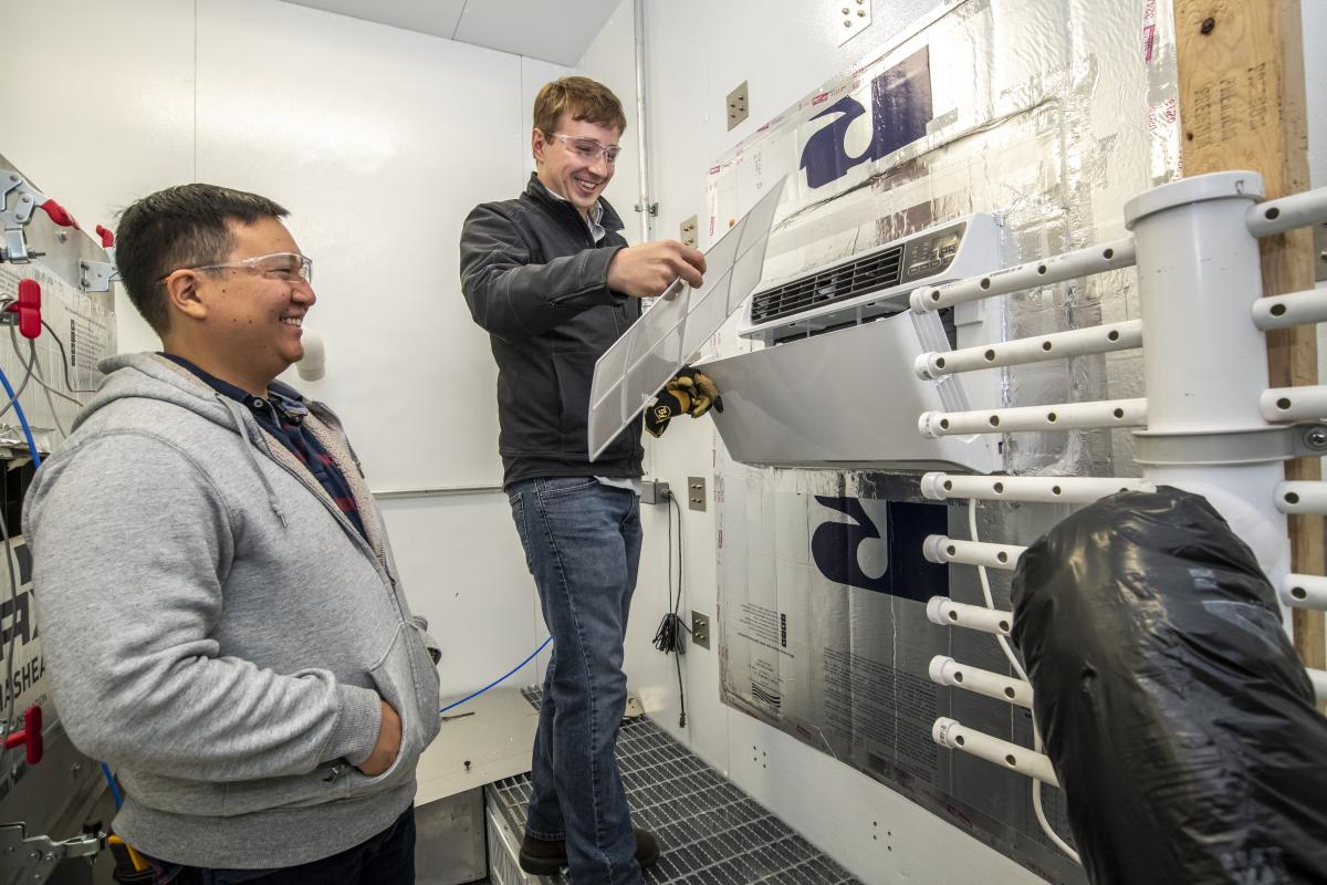Tom Burke and Kevin Zhou test an air conditioner.