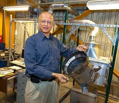 Ashok Gadgil holds stove equipment at Berkeley Lab's facility.